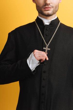 Photo pour Vue partielle du prêtre catholique touchant croix sur son collier isolé sur jaune - image libre de droit