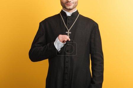 Photo pour Vue recadrée du prêtre catholique touchant croix sur son collier isolé sur jaune - image libre de droit