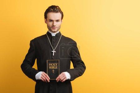 Photo pour Jeune prêtre catholique confiant regardant la caméra tout en tenant la bible isolée sur jaune - image libre de droit