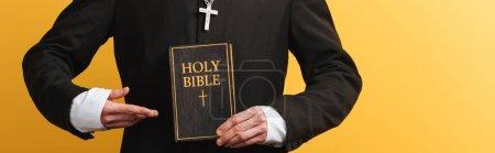Photo pour Vue partielle du prêtre catholique pointant du doigt la sainte bible isolée sur un plan panoramique jaune - image libre de droit