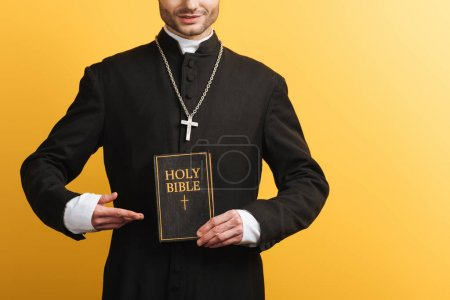 Photo pour Vue recadrée du prêtre catholique pointant du doigt la sainte bible isolée sur jaune - image libre de droit