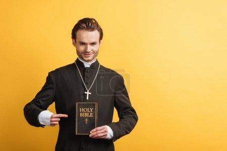 Photo pour Prêtre catholique souriant pointant du doigt la bible sainte tout en regardant la caméra isolée sur jaune - image libre de droit