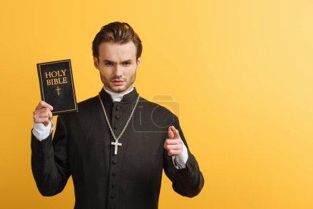 Photo pour Sérieux prêtre catholique pointant du doigt la caméra tout en tenant la bible isolée sur jaune - image libre de droit