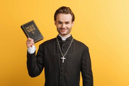 Photo pour Heureux prêtre catholique tenant la bible tout en souriant à la caméra isolée sur jaune - image libre de droit