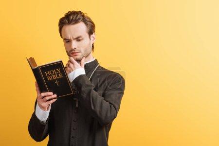 Photo pour Prêtre catholique concentré touchant le visage tout en lisant la bible isolée sur jaune - image libre de droit