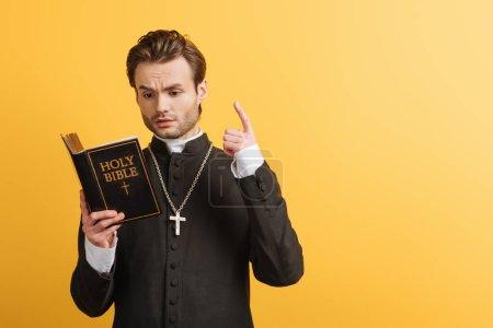 Photo pour Prêtre catholique réfléchi montrant signe idée tout en lisant la bible isolé sur jaune - image libre de droit