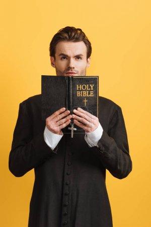 Photo pour Prêtre catholique réfléchi levant les yeux tout en tenant la bible ouverte isolé sur jaune - image libre de droit
