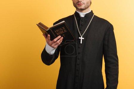 Photo pour Vue recadrée du prêtre catholique lisant la bible isolée sur jaune - image libre de droit