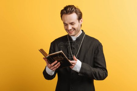 Photo for Cheerful catholic priest laughing while reading bible isolated on yellow - Royalty Free Image