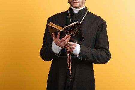 Photo pour Vue recadrée du prêtre catholique lisant la bible et tenant des perles de chapelet en bois isolées sur jaune - image libre de droit