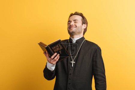 Photo pour Excité prêtre catholique riant tout en tenant la bible sainte isolé sur jaune - image libre de droit