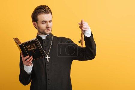 Photo pour Prêtre catholique réfléchi tenant la bible et regardant des perles de chapelet en bois isolé sur jaune - image libre de droit