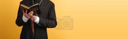 Photo pour Vue recadrée du prêtre catholique lisant la bible tout en tenant des perles de chapelet en bois isolées sur plan panoramique jaune - image libre de droit