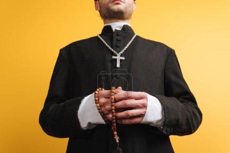 Photo pour Vue à angle bas du prêtre catholique tenant des perles de chapelet en bois isolées sur jaune - image libre de droit