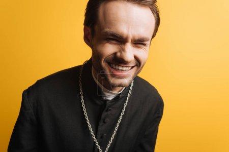 Photo pour Excité prêtre catholique rire en regardant la caméra isolée sur jaune - image libre de droit