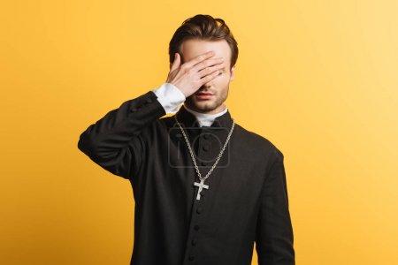 Photo pour Jeune prêtre catholique couvrant les yeux avec la main isolé sur jaune - image libre de droit