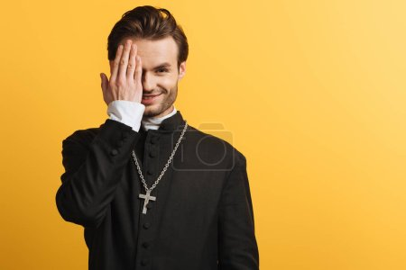 Photo for Smiling catholic priest covering eye with hand while looking at camera isolated on yellow - Royalty Free Image