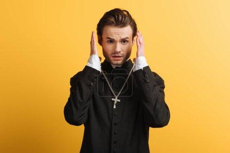 Photo pour Prêtre catholique choqué tenant la main près de la tête et regardant la caméra isolée sur jaune - image libre de droit