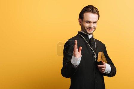 Photo pour Prêtre catholique souriant montrant un geste de bénédiction tout en tenant la bible isolée sur jaune - image libre de droit
