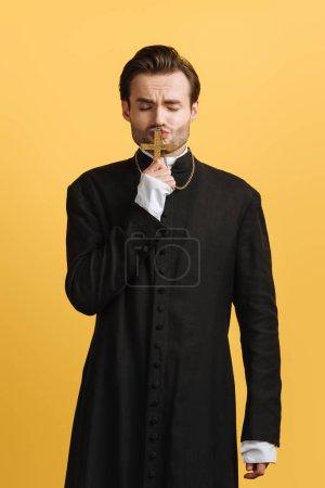 Photo pour Jeune prêtre catholique fidèle embrasser croix avec les yeux fermés isolé sur jaune - image libre de droit