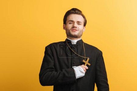Photo pour Jeune prêtre catholique épuisé tenant la croix près du coeur isolé sur jaune - image libre de droit
