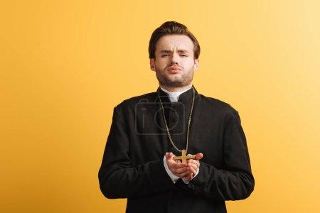 Photo pour Jeune prêtre catholique avec l'expression du visage ennuyé tenant la croix et regardant la caméra isolée sur jaune - image libre de droit