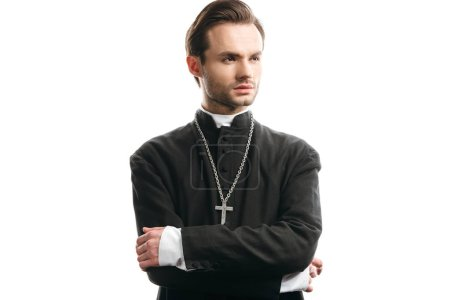Photo for Young, confident catholic priest looking away while standing with crossed arms isolated on white - Royalty Free Image
