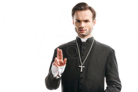 Photo pour Confiant, prêtre catholique strict montrant geste de bénédiction isolé sur blanc - image libre de droit