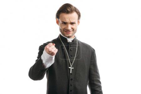 Photo pour Prêtre catholique agressif montrant poing tout en regardant la caméra isolée sur blanc - image libre de droit