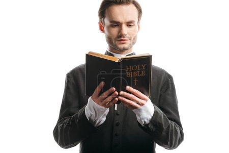 ernster, konzentrierter katholischer Priester liest Bibel isoliert auf weißem Papier