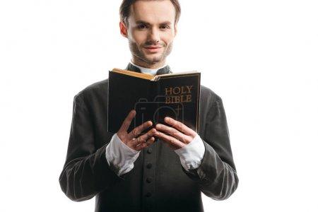 Photo pour Jeune prêtre catholique souriant tenant la bible sainte tout en regardant la caméra isolée sur blanc - image libre de droit
