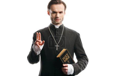 Photo pour Confiant, prêtre catholique strict tenant la bible sainte et montrant geste de bénédiction isolé sur blanc - image libre de droit