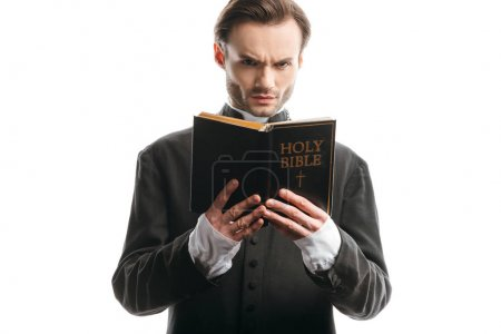 frunciendo el ceño sacerdote católico mirando a la cámara mientras sostiene la sagrada Biblia aislada en blanco