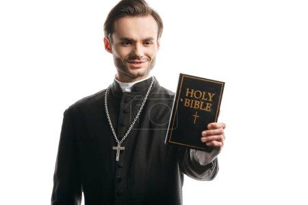 Photo pour Jeune prêtre catholique souriant tout en tenant la bible sainte isolé sur blanc - image libre de droit