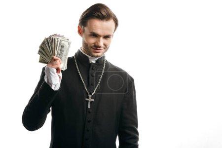 Photo pour Prêtre catholique corrompu souriant à la caméra tout en tenant des billets en dollars isolés sur blanc - image libre de droit