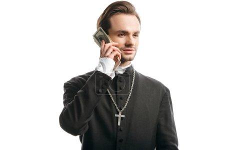 Photo pour Prêtre catholique corrompu regardant loin tout en tenant l'argent près du visage isolé sur blanc - image libre de droit