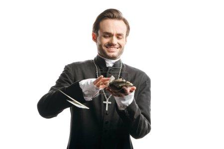 Photo pour Un prêtre catholique corrompu souriant tout en comptant de l'argent isolé sur - image libre de droit