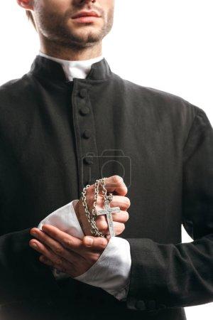 Photo pour Vue recadrée du jeune prêtre catholique tenant collier avec croix d'argent isolé sur blanc - image libre de droit