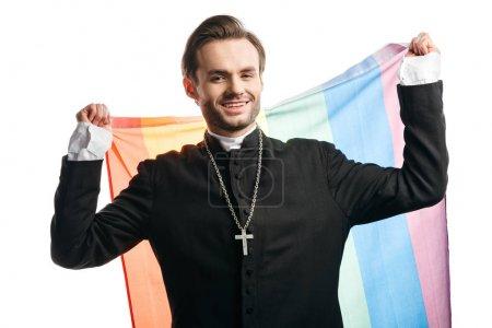 Photo pour Prêtre catholique souriant regardant la caméra tout en tenant le drapeau lgbt isolé sur blanc - image libre de droit