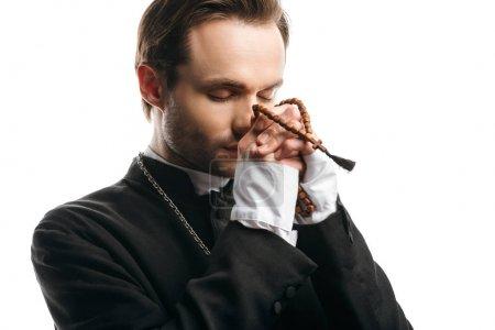 Photo pour Jeune prêtre catholique concentré priant les yeux fermés en tenant des perles de rosaire près du visage isolé sur blanc - image libre de droit