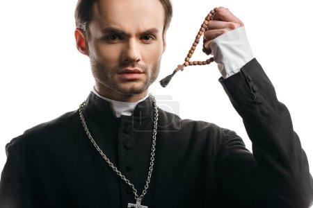Photo pour Jeune prêtre catholique sérieux tenant des perles de chapelet en bois tout en regardant la caméra isolée sur blanc - image libre de droit