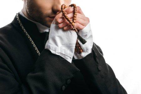 Photo pour Vue partielle du prêtre catholique priant tout en tenant des perles de chapelet en bois près du visage isolé sur blanc - image libre de droit