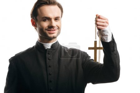 Photo for Happy catholic priest holding golden cross while looking at camera isolated on white - Royalty Free Image