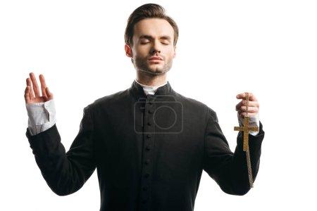 Photo pour Prêtre catholique concentré priant avec la main levée tout en tenant la croix d'or isolé sur blanc - image libre de droit