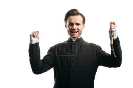 Photo pour Prêtre catholique en colère criant à la caméra tout en tenant le poing levé et la croix d'or isolé sur blanc - image libre de droit