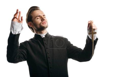 Photo pour Jeune prêtre catholique priant les yeux fermés et les mains levées en tenant la croix d'or isolé sur le blanc - image libre de droit