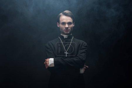 Photo pour Jeune prêtre catholique sérieux debout avec les bras croisés sur fond noir avec de la fumée - image libre de droit