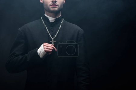 Photo for Cropped view of catholic priest touching silver cross on his necklace on black background with smoke - Royalty Free Image