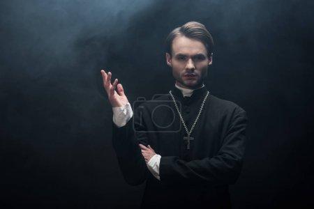 Photo pour Jeune prêtre catholique confiant debout avec bras ouvert sur fond noir avec de la fumée - image libre de droit