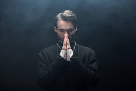 Photo for Young concentrated catholic priest praying with closed eyes on black background with smoke - Royalty Free Image